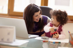 Multitasking Mother With Her Daughter Royalty Free Stock Photos