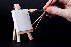 Multitasking painter with small easel and canvas Royalty Free Stock Images