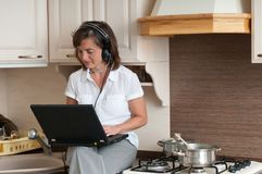 Multitasking - preparing meal and working Stock Images