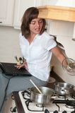 Multitasking - preparing meal and working Stock Image