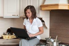 Multitasking - preparing meal and working Stock Photos