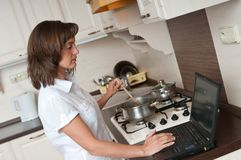 Multitasking - preparing meal and working Royalty Free Stock Photo
