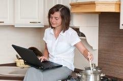 Multitasking - preparing meal and working Royalty Free Stock Photos