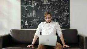 multitasking Przystojny młody człowiek jest ubranym szkła i działanie z touchpad podczas gdy siedzący na leżance w biurze 20s 4k zdjęcie wideo