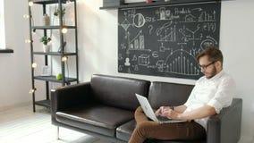 multitasking Przystojny młody człowiek jest ubranym szkła i działanie z touchpad podczas gdy siedzący na leżance w biurze 20s 4k zbiory wideo