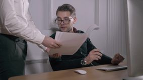 multitasking Stiliga bärande exponeringsglas för ung man och funktionsduglig withlaptop, medan sitta i modernt kontor Freelancer  arkivfilmer