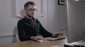 multitasking Stiliga bärande exponeringsglas för ung man och funktionsduglig withlaptop, medan sitta i modernt kontor Freelancer  lager videofilmer