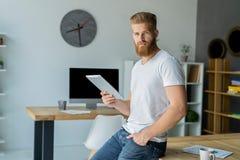 multitasking Vidros vestindo consideráveis do homem novo e trabalho com touchpad ao sentar-se no sofá no escritório Imagem de Stock Royalty Free