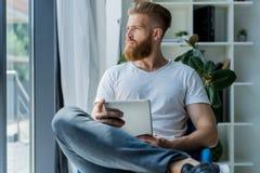 multitasking Vidros vestindo consideráveis do homem novo e trabalho com touchpad ao sentar-se no sofá no escritório Fotos de Stock Royalty Free