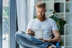 multitasking Vidros vestindo consideráveis do homem novo e trabalho com touchpad ao sentar-se no sofá no escritório Fotografia de Stock Royalty Free