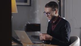 multitasking Vidros vestindo consideráveis do homem novo e withlaptop de trabalho ao sentar-se no escritório moderno Freelancer d video estoque