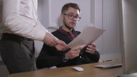 multitasking Vidros vestindo consideráveis do homem novo e withlaptop de trabalho ao sentar-se no escritório moderno Freelancer d filme
