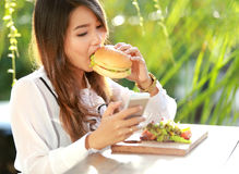 Multitasking woman having lunch while texting on her mobilephone Royalty Free Stock Photo