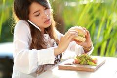Multitasking woman talking on the phone while eating burger Stock Photos