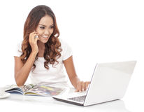 Multitasking woman talking on the phone while working on her lap Stock Images