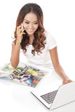 Multitasking woman talking on the phone while working on her lap Royalty Free Stock Photos