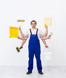 Multitasking worker ready to paint the room Royalty Free Stock Photos