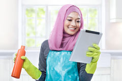 Multitasking young housewife using tablet while carrying a bottl Royalty Free Stock Image