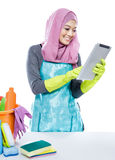 Multitasking young housewife using tablet while cleaning a table Stock Images