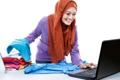 Multitasking young woman wearing hijab watching movie on laptop Stock Photos
