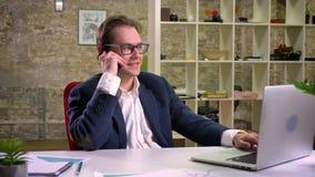 Multitaskingaffärsmannen talar över smartphonen och skriver på bärbara datorn, med leende och ljus kopplat av lynne stock video