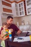 Multitaskingfadern är babysitting och arbeta hemma royaltyfri bild
