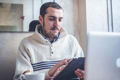 Multitaskingman som använder minnestavlan, bärbara datorn och cellhpone Arkivfoton