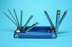 Multitool in a blue background. Close view of multi function tool in a blue background Royalty Free Stock Image