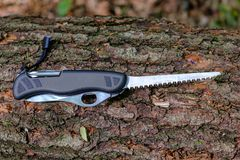 Free Multitool Outdoor Equipment, Swiss Soldier`s Knife With Extended Saw Blade On Tree Trunk In Forest Stock Photos - 148030433