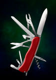 Multitools penknife. With red handle against green background Royalty Free Stock Photos
