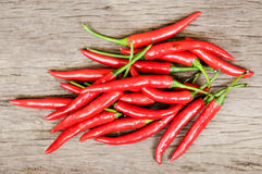 Multitude of red chili peppers on wooden table Royalty Free Stock Photos