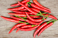 Multitude of red chili peppers on wooden table Royalty Free Stock Photography