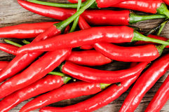 Multitude of red chili peppers on wooden table Stock Images