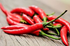 Multitude of red chili peppers on wooden table Royalty Free Stock Image