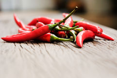 Multitude of red chili peppers on wooden table Stock Photo
