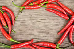 Multitude of red chili peppers on wooden table Stock Photos