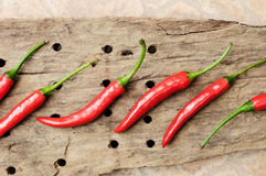 Multitude of red chili peppers on wooden table Royalty Free Stock Photo