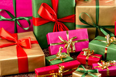 Multitude of Wrapped Gifts. Plain-colored presents with bows in gold, red and green. Tightly framed, shallow depth of field. Background for gift-giving occasion Royalty Free Stock Photography