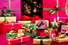 Multitude of Xmas Gifts Spread Out. Plenty of single-colored Christmas presents placed on a red, smooth cloth. Vibrant colors. Narrow depth of field. Blurred Stock Image