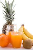 Multivitamin juice. Jug and glass of multivitamin juice with fruits Royalty Free Stock Image