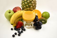 Multivitamin juice stock images. Glass of multivitamin juice with fruits. Multivitamin juice with fruits on a white background. Various fruits images Stock Image