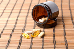 Multivitamin Pills in a brown medicine jar Stock Photos