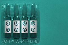 Multivitamins hanterend concept Vier ampules met bekledingsbrieven van elementen van de inschrijvingsa. C. de E-N K pp B6 B12 vit stock afbeelding