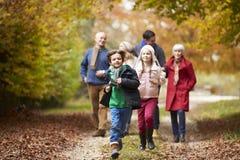 Multl utvecklingsfamilj som promenerar Autumn Path Arkivfoto