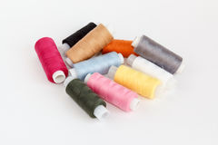 Multy coloured bobbins of thread on white. Background Stock Photography