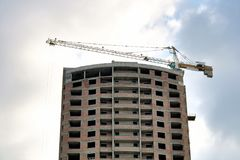 The multystoried residential building in the course of construction whith crane. The multystoried residential building in the course of construction with crane royalty free stock images