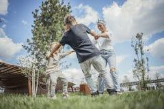 Mum που γυρίζει γύρω, που και που έχει τη διασκέδαση με τους γιους της στο πάρκο στοκ εικόνες