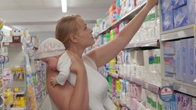 Mum with baby buying things in household goods section of supermarket stock footage