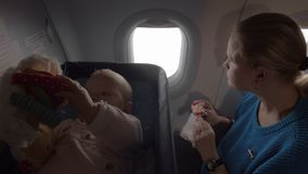 Air travel of mum with baby daughter. Mum with baby traveling by plane. Playful child lying with toy in special bassinet while mother having a snack and stock video footage