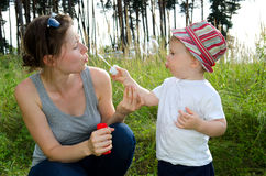 Mum blowing bubbles for son Royalty Free Stock Image